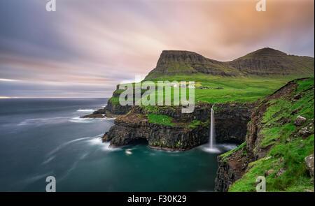 Gasadalur village and its iconic waterfall, Vagar, Faroe Islands, Denmark. Long exposure. - Stock Photo