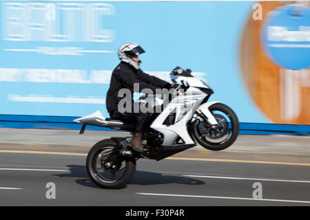Liverpool, Merseyside, UK  27th September, 2015. Motorcyclist wheelies, popping a wheelie on the Strand as Police - Stock Photo