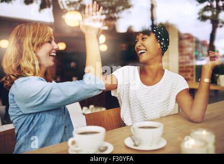 Happy exuberant young girl friends giving a high five slapping each others hand in congratulations as they sit together - Stock Photo