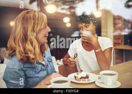 Two good female friends enjoying a cup of coffee together in a coffee house with one laughing as the other makes - Stock Photo
