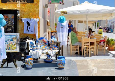 Tourists enjoying a drink outside a street cafe next to a souvenir shop in the village of Oia Santorini greece - Stock Photo