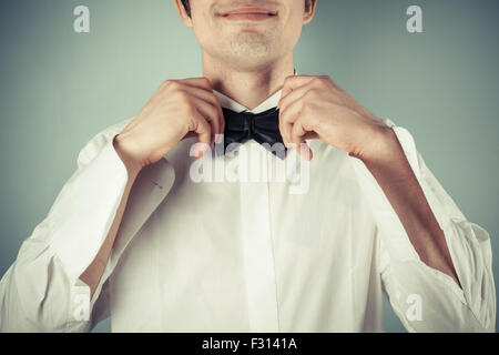 Closeup on a happy young man tying a bow tie - Stock Photo