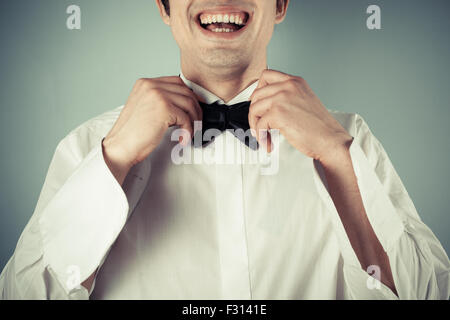 Closeup on a happy and smiling young man tying a bow tie - Stock Photo