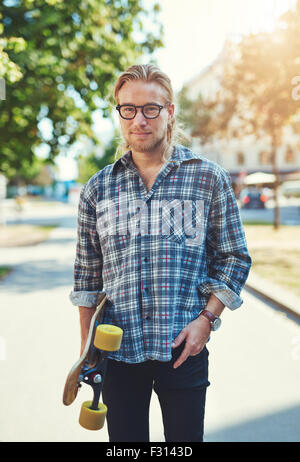 Portrait of cool young man with long hair and glasses carrying a skateboard - Stock Photo