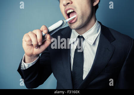 Young businessman is brushing his teeth with an electric toothbrush - Stock Photo