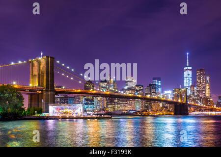 Beautiful Brooklyn Bridge across the East River toward Manhattan New York City lit up. - Stock Photo