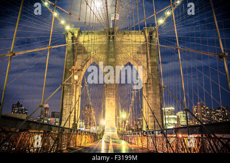 View of historic Brooklyn Bridge at night seen from the pedestrian walkway - Stock Photo