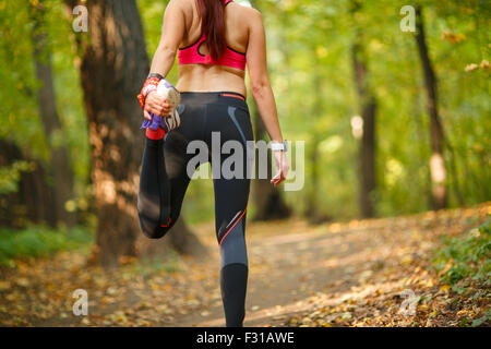 Detail of man stretching legs before jogging in autumn nature - Stock Photo