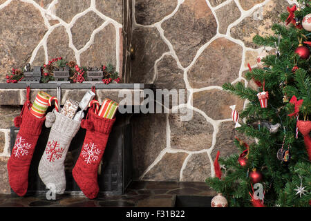 ... Stockings hanging on a fireplace next to a christmas tree on christmas  morning - Stock Photo