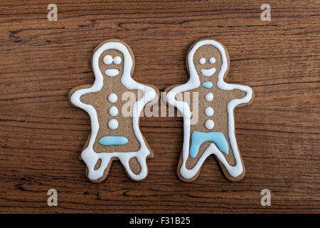 Gingerbread man and woman on a wooden background - Stock Photo