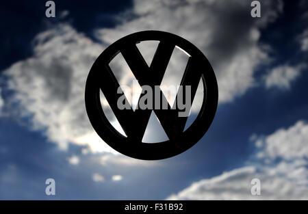 VW VOLKSWAGEN CAR BADGE AGAINST STORMY SKY RE EMISSIONS SCANDAL DIRTY DIESEL ENGINES MOTOR INDUSTRY STORY LOGO EMBLEM - Stock Photo