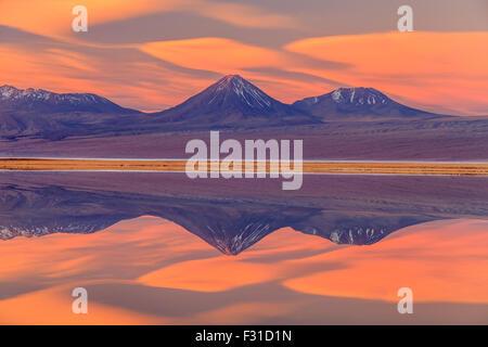 Volcan Licancabur reflected in Laguna Tebinquinche at sunset - Stock Photo