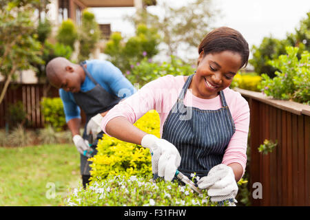 attractive young African woman gardening with her husband at home - Stock Photo