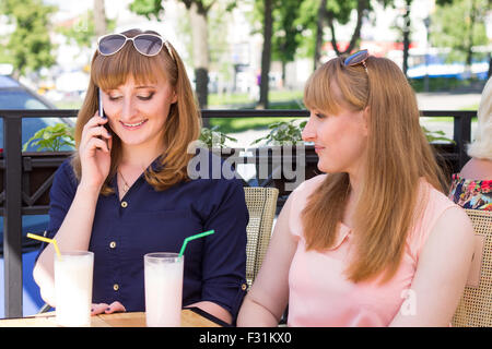 Twins sisters have coctails at the restaurant. Young student girls chatting in cafe at summer day - Stock Photo