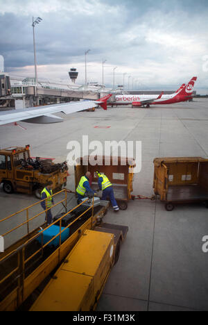 Baggage handers unloading baggage from an Air Berlin flight at Munich Airport, Germany. - Stock Photo