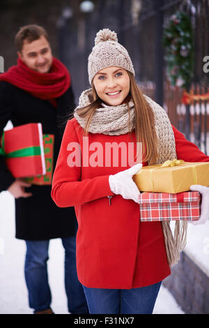 Happy woman with presents looking at camera on background of young man outdoors - Stock Photo