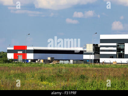Large industrial facility with  the stock of the construction equipment nearby - Stock Photo