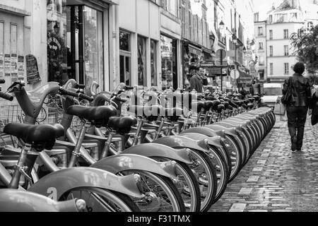 Rental bikes in a row on a street in Paris, France - Stock Photo