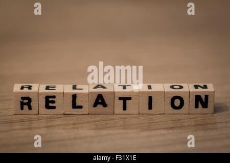 relation written in wooden cubes on a desk - Stock Photo