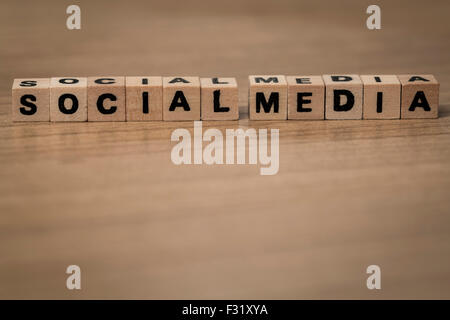 Social Media written in wooden cubes on a desk - Stock Photo