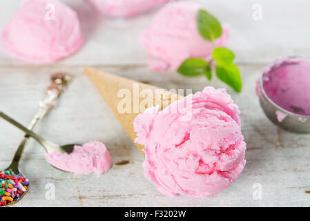 Pink ice cream in waffle cone with utensil on rustic wooden background. - Stock Photo