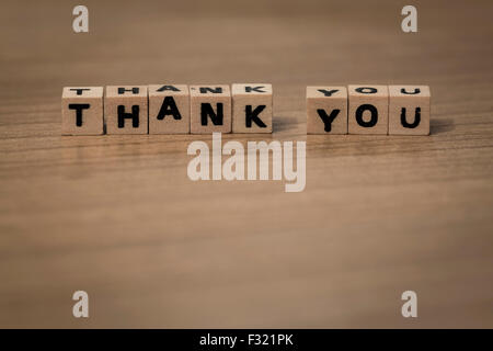 thank you written in wooden cubes on a desk - Stock Photo