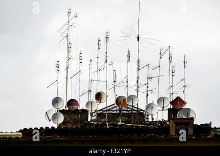 Multiple satellite dishes and television aerials on top of an apartment building. - Stock Photo