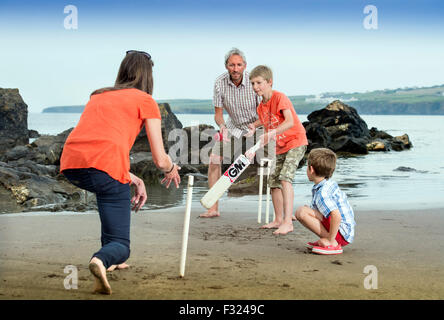 A family play beach cricket at Poppit Sands near St Dogmaels, Pembrokeshire, Wales UK - Stock Photo