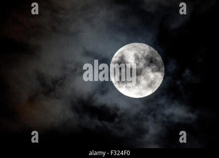 Athens, Greece. 27th Sep, 2015. The Fullmoon is seen rising over the cloudy sky of Athens, Greece, on 27 September - Stock Photo