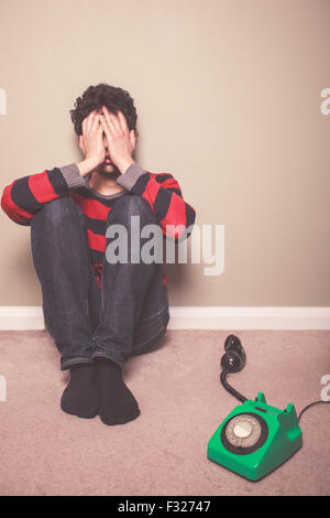 Tired and sad young man is sitting on the floor with a telephone