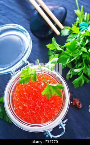 red salmon caviar in glass bank and on a table - Stock Photo