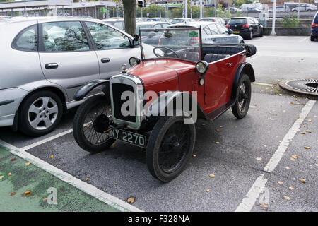 A small vintage Austin 7 car in a car park with larger modern saloon cars. - Stock Photo