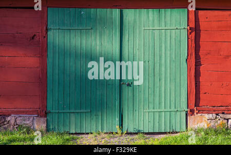 Image of green doors on a red barn. - Stock Photo