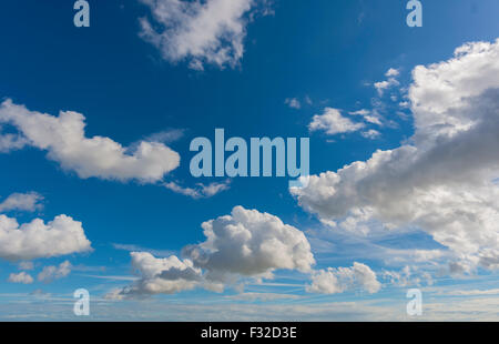 White fluffy cumulus clouds floating in a deep blue sky - Stock Photo