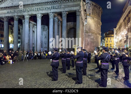 Marching ban with brass instruments performs in front of the Pantheon in Rome Italy at night as crowd looks on. - Stock Photo