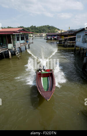 Water taxi speedboat passing shacks on stilts in river, Water Village (Kampong Ayer), Brunei River, Bandar Seri - Stock Photo