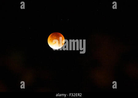Godalming, UK. 28th Sep, 2015. The moon turns an orange colour during a lunar eclipse seen over Godalming in Surrey, - Stock Photo