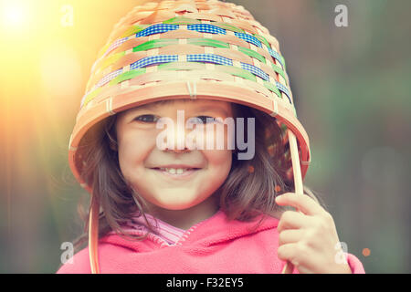 Happy smiling little girl wearing picnic basket outdoors - Stock Photo