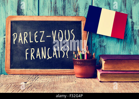 a chalkboard with the question parlez-vous francais? do you speak french? written in french, a pot with pencils - Stock Photo