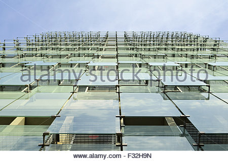 Modern office building glass facade cladding low angle viewpoint, Barcelona Spain Europe - Stock Photo