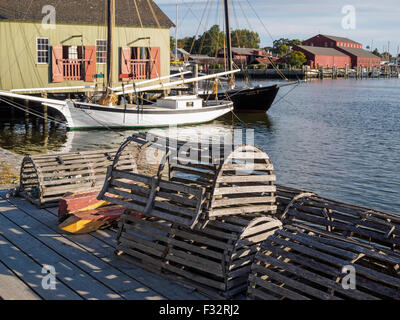 Historic Mystic Seaport Connecticut in autumn with lobster boxes traps tall ships Nellie and Regina M docked on - Stock Photo