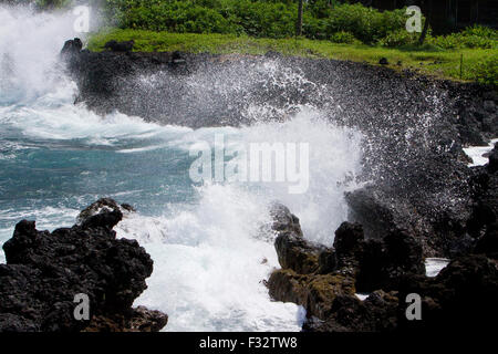 Waves crashing against rocks along the shoreline at Keanae Peninsula, just off Hana Highway, Maui, Hawaii in August - Stock Photo