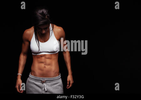 Image of fitness woman in sports clothing looking down. Young female model with muscular body. Horizontal studio - Stock Photo