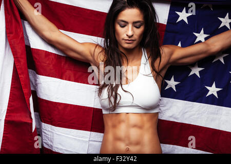 Portrait of muscular female holding American Flag. Fit young woman wearing sports bar holding United States of American - Stock Photo