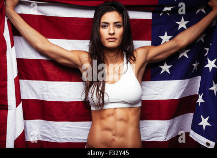 Portrait of proud female athlete holding American Flag against. Muscular young woman looking confidently at camera. - Stock Photo