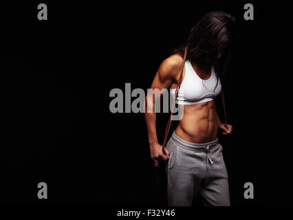 Portrait of woman athlete holding jumping rope looking down against black background. Female with muscular body - Stock Photo