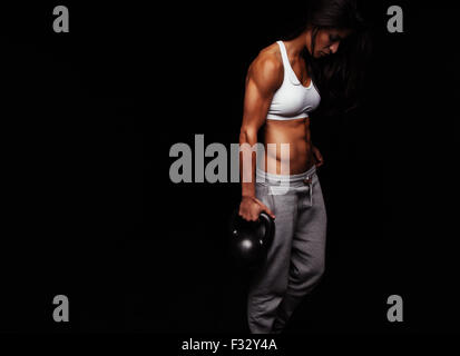 Muscular woman doing crossfit exercise. Tough fitness female model with kettle bell on black background. - Stock Photo