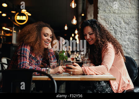 Young women sitting at cafe and using phone. Friends sitting in a restaurant with one woman showing something interesting - Stock Photo