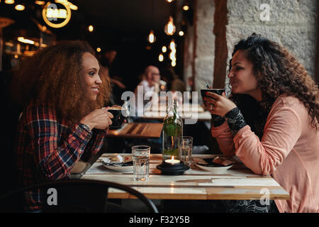 Side view portrait of two young women talking and drinking coffee in a cafe. Female friends in a restaurant. - Stock Photo
