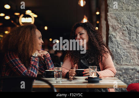 Two women discussing at a restaurant smiling. Young friends sitting in a cafe and talking. - Stock Photo